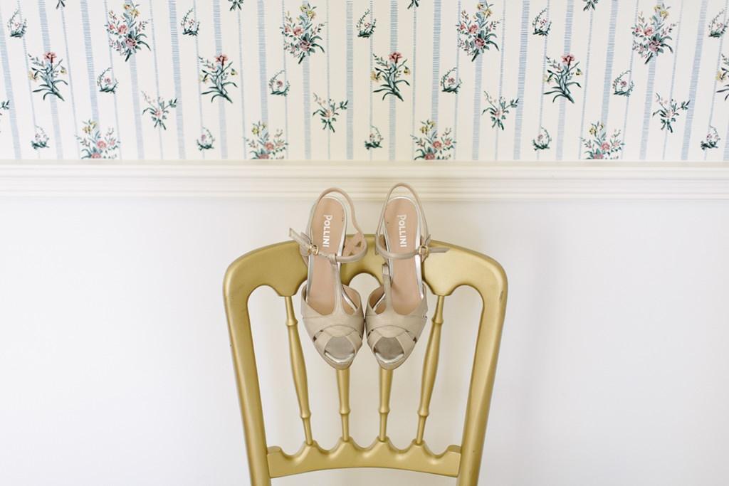 Brautschuhe hängen an einem goldenen Stuhl