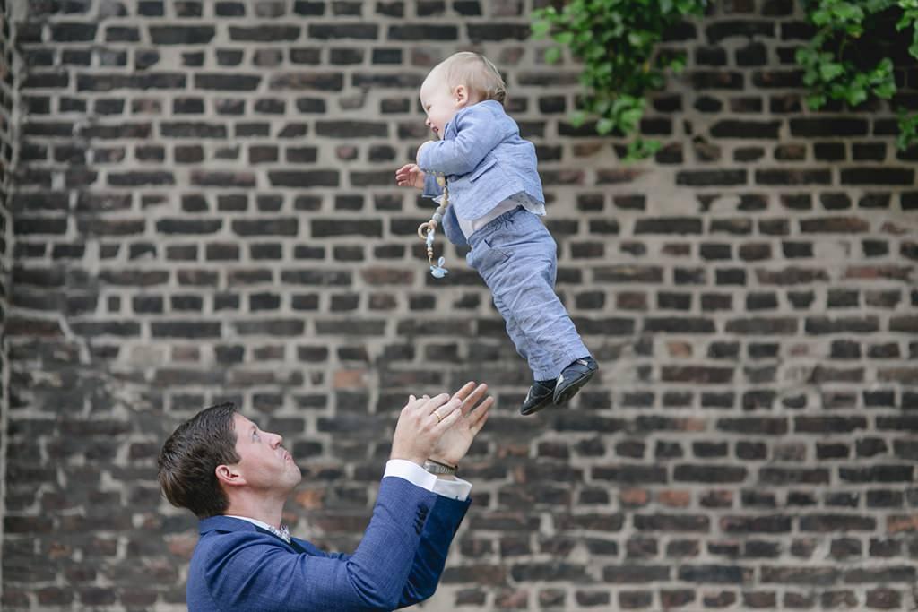 der Bräutigam wirft ausgelassen sein Kind in die Luft