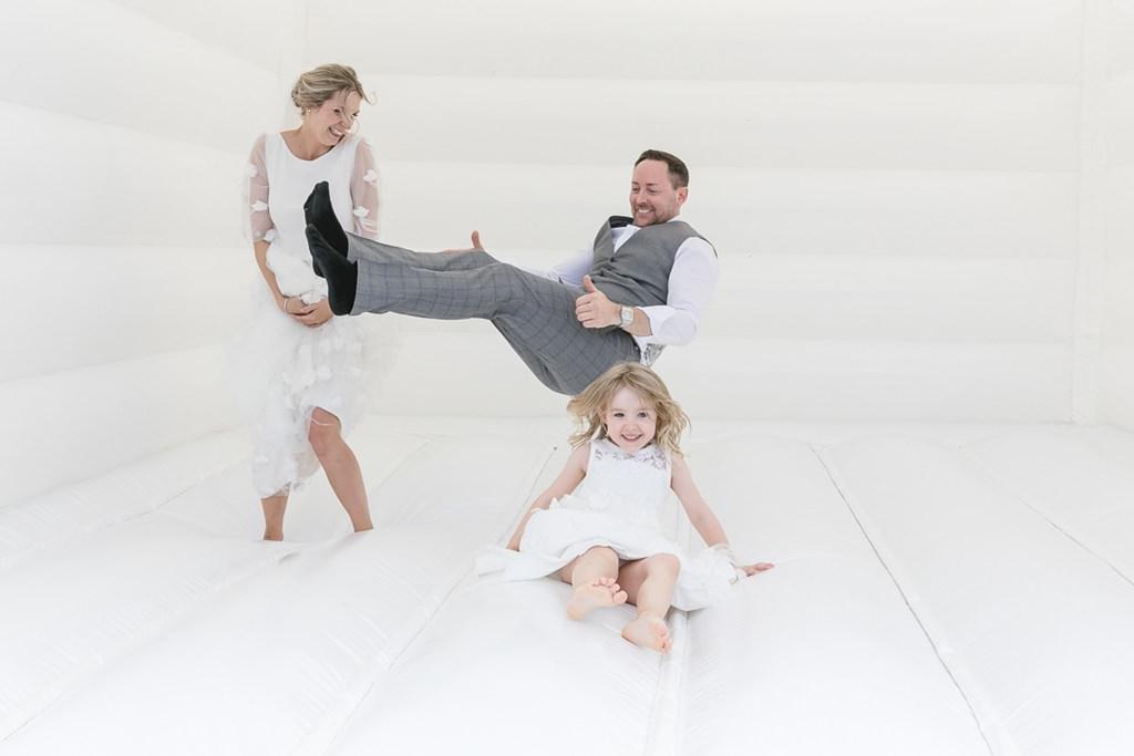 Braut und Bräutigam hüpfen mit ihrer Tochter auf einer Hüpfburg