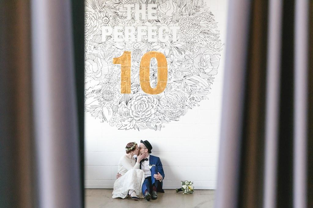 Braut und Bräutigam sitzen auf dem Boden und küssen sich