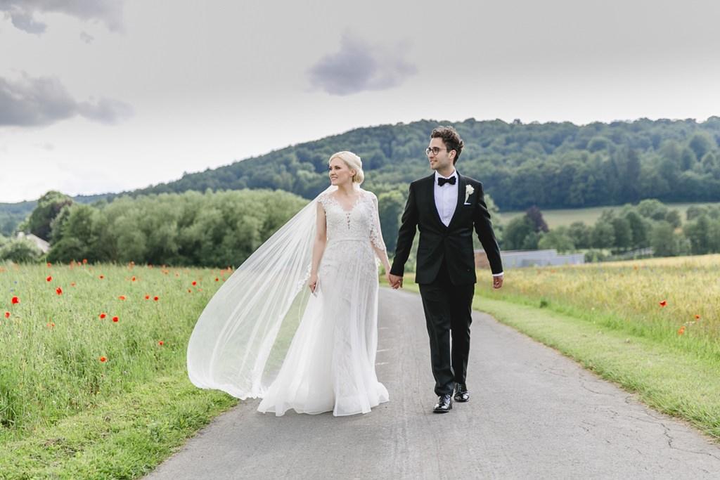 Braut und Bräutigam laufen über einen Feldweg