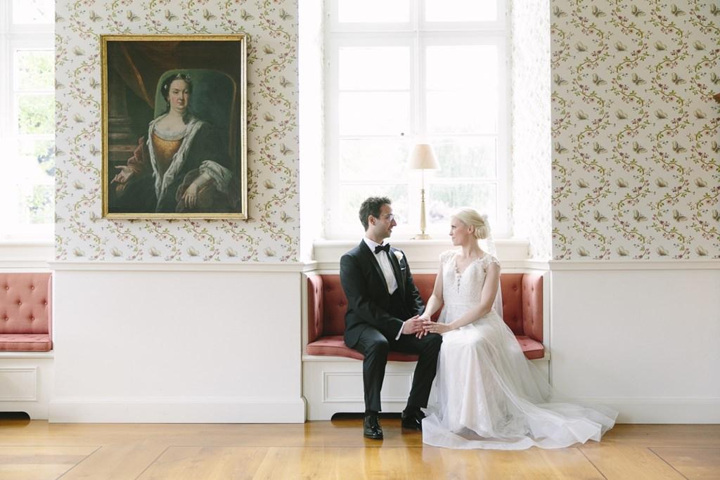 Braut und Bräutigam sitzen auf einem Sofa und halten sich an den Händen