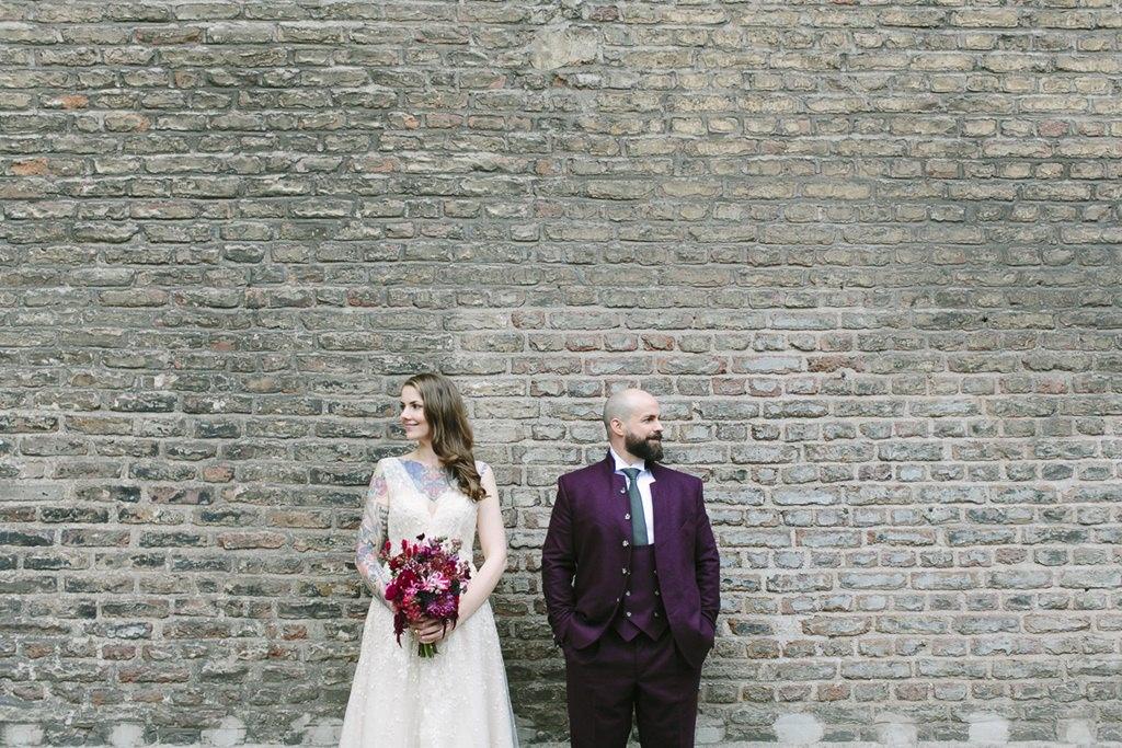 Braut und Bräutigam stehen vor einer Backsteinmauer