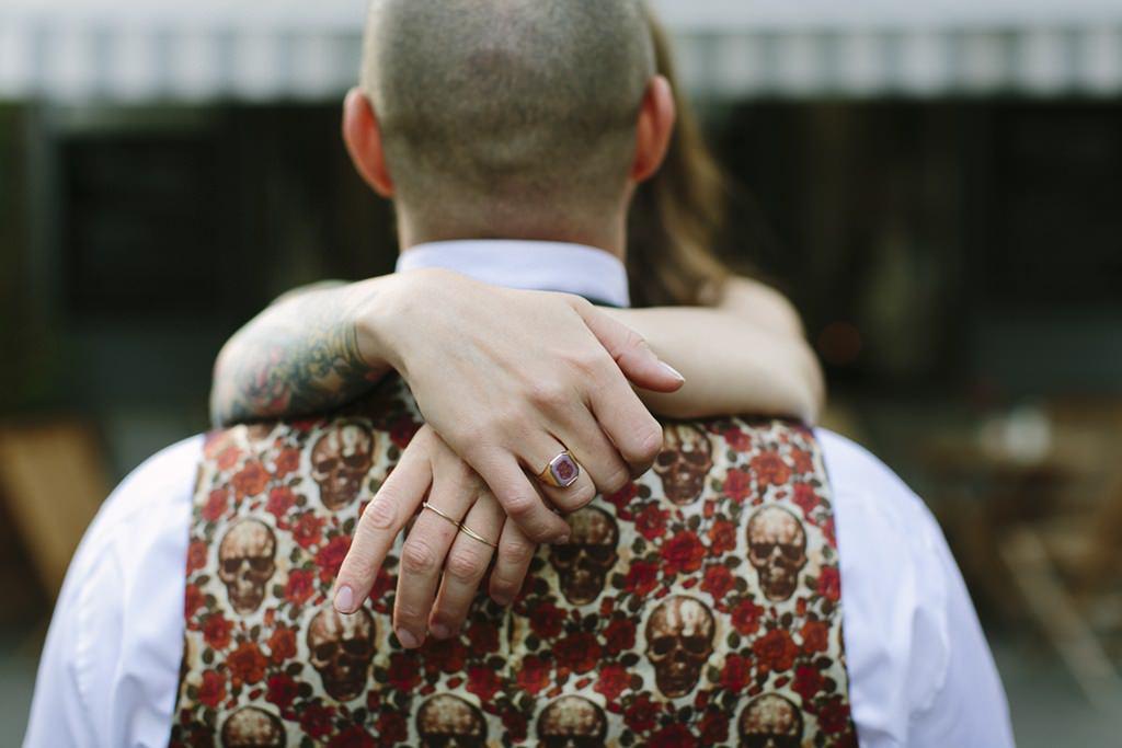 der Bräutigam trägt eine Weste mit Totenköpfen und Rosen und wird von seiner Braut umarmt