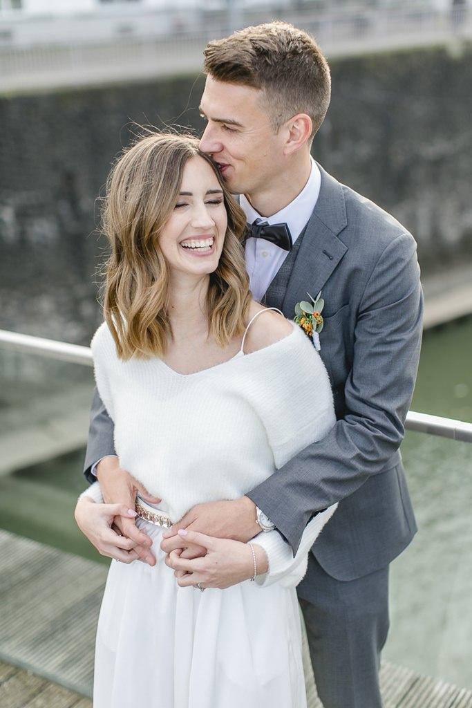der Bräutigam umarmt die Braut von hinten und küsst sie zärtlich auf die Stirn
