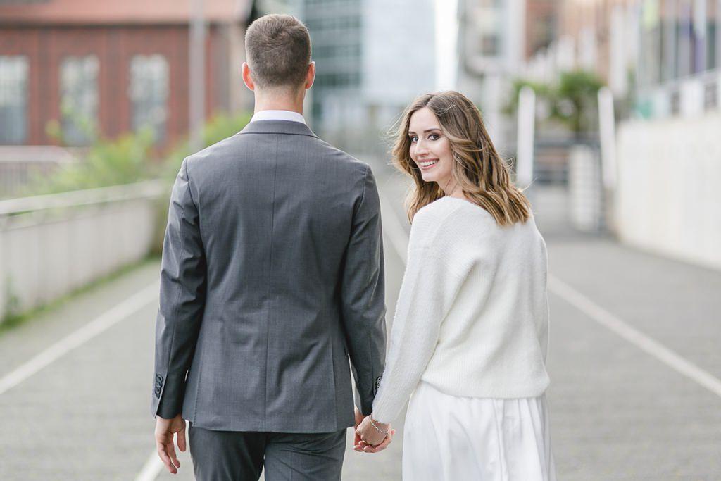 die Braut schaut über die Schulter, während der Bräutigam nur von hinten zu sehen ist