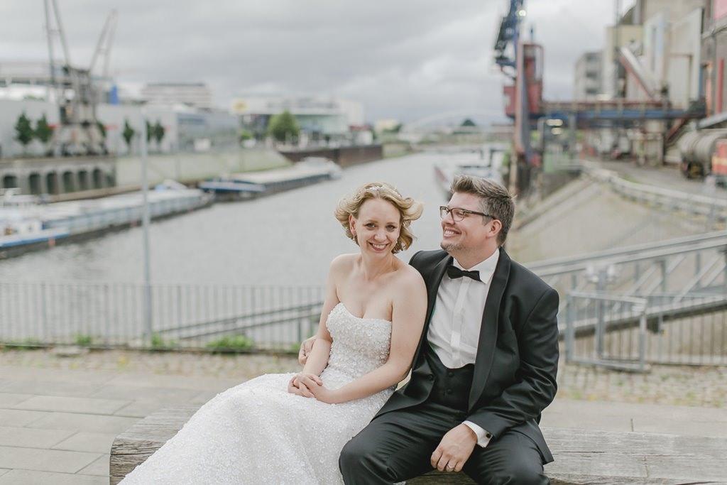Braut und Bräutigam sitzen vor einem Fluss