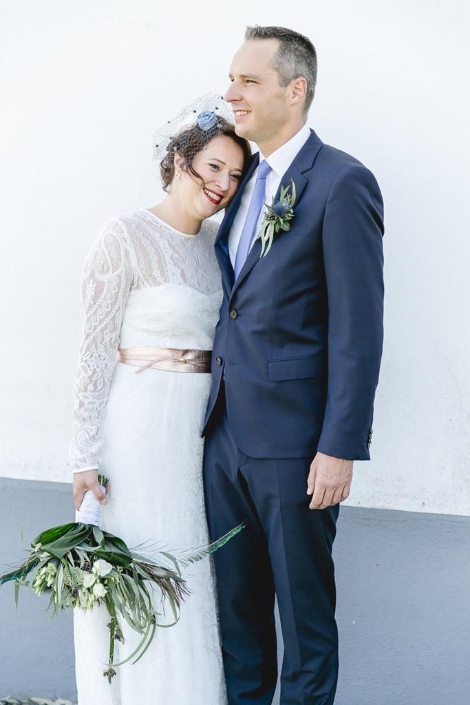 Braut und Bräutigam stehen Arm in Arm an der Kirche