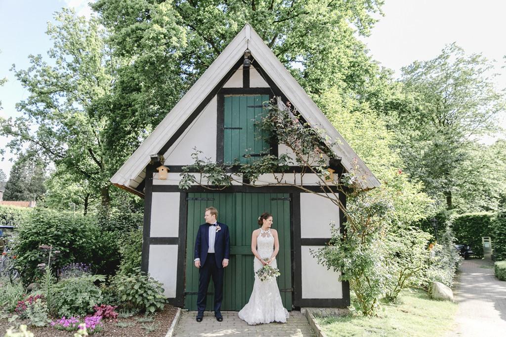 Paarfoto vor einem kleinen Gartenhaus