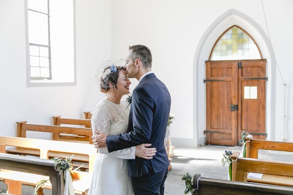 der Bräutigam küsst die Braut in der Kirche auf die Stirn