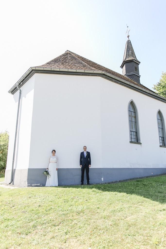 Braut und Bräutigam posieren für ein Paarfoto vor der Kirche