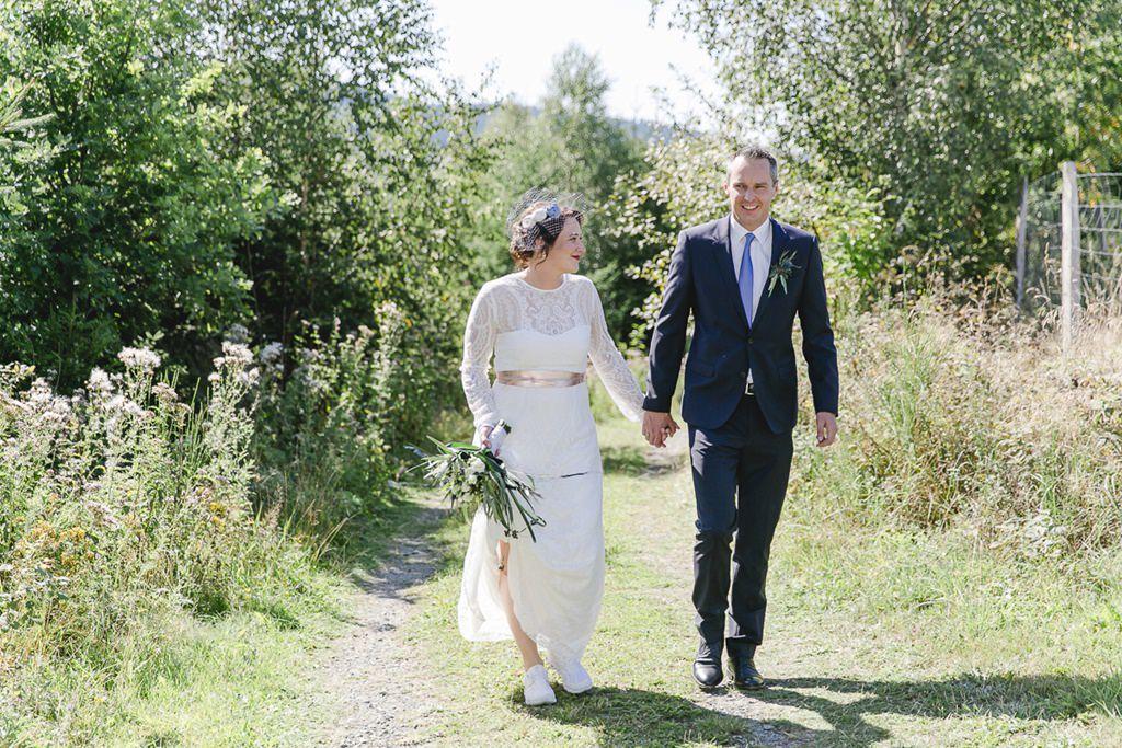 Braut und Bräutigam laufen Hand in Hand auf einem Feldweg