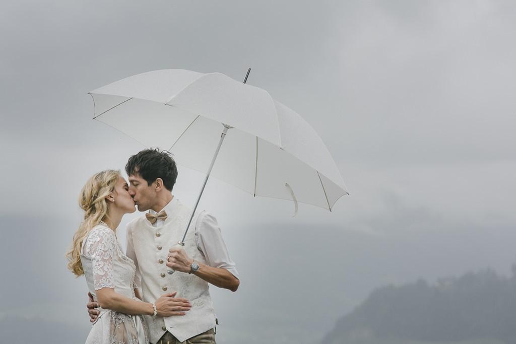 Braut und Bräutigam küssen sich unter einem Regenschirm