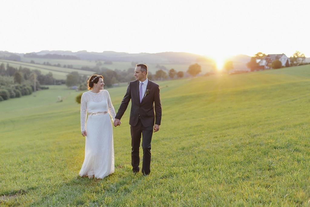 Braut und Bräutigam laufen über eine Wiese mit dem Sonnenuntergang im Hintergrund