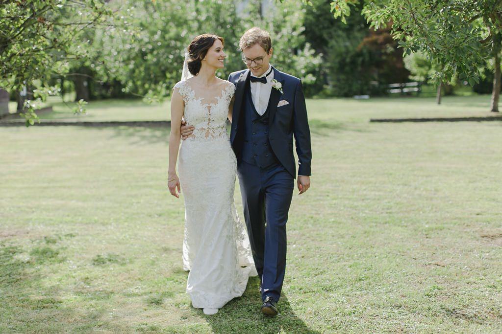 Braut und Bräutigam laufen Arm in Arm über eine Wiese