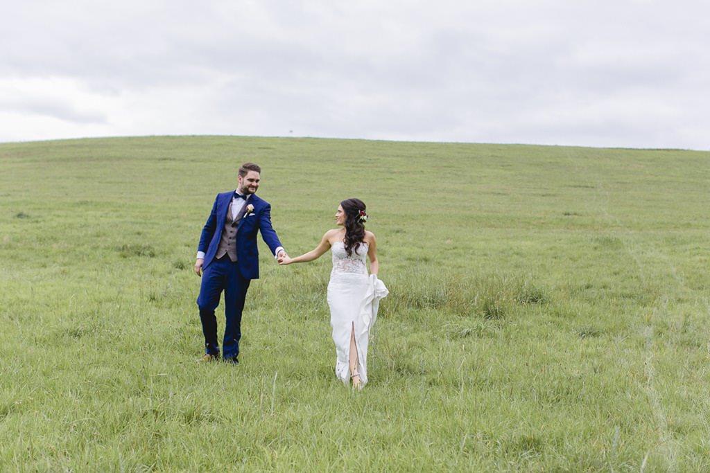 Braut und Bräutigam laufen Hand in Hand über eine grüne Wiese