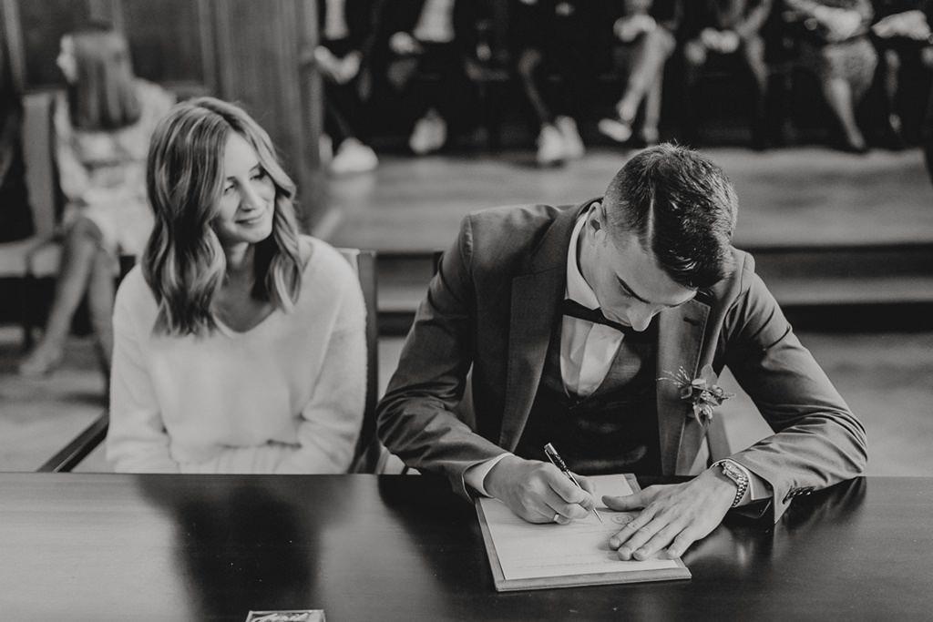 der Bräutigam unterschreibt bei der standesamtlichen Trauung