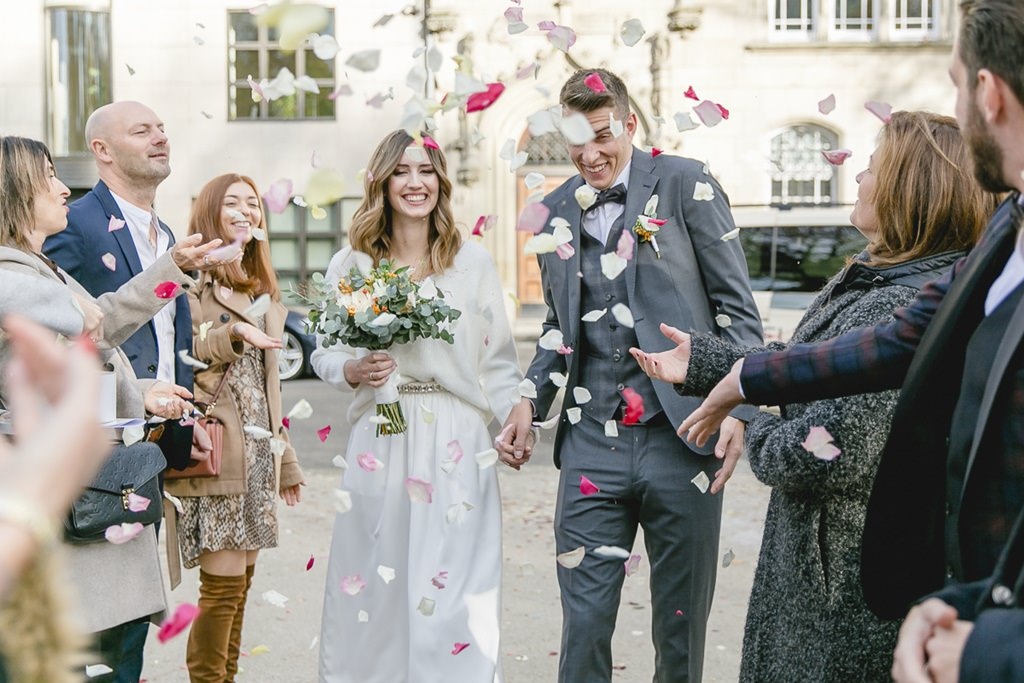 Braut und Bräutigam wreden nach der standesamtlichen Trauung mit Rosenblättern beworfen