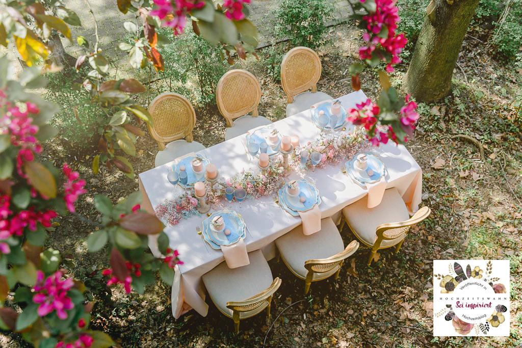 gedeckter Tisch mit Deko in Rosa, Blau und Weiß, der in einem Sommer-Garten steht