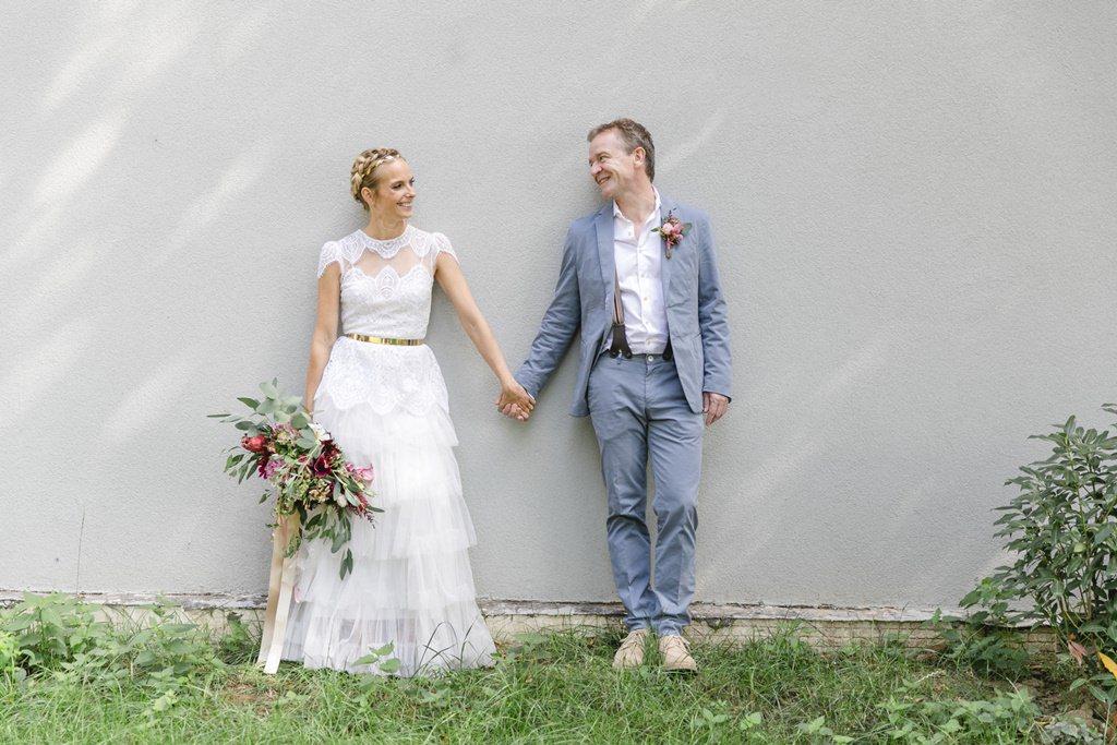 Paarfoto von Braut und Bräutigam, die Hand in Hand vor einer grauen Wand stehen