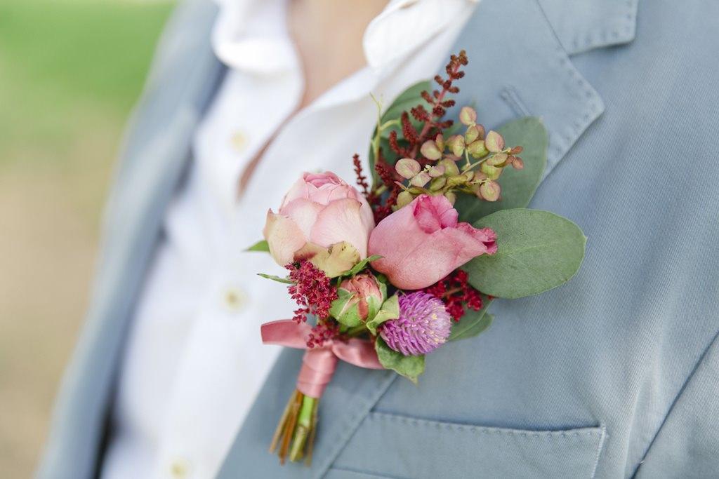 Blumenanstecker mit Rosen am Sakko des Bräutigams