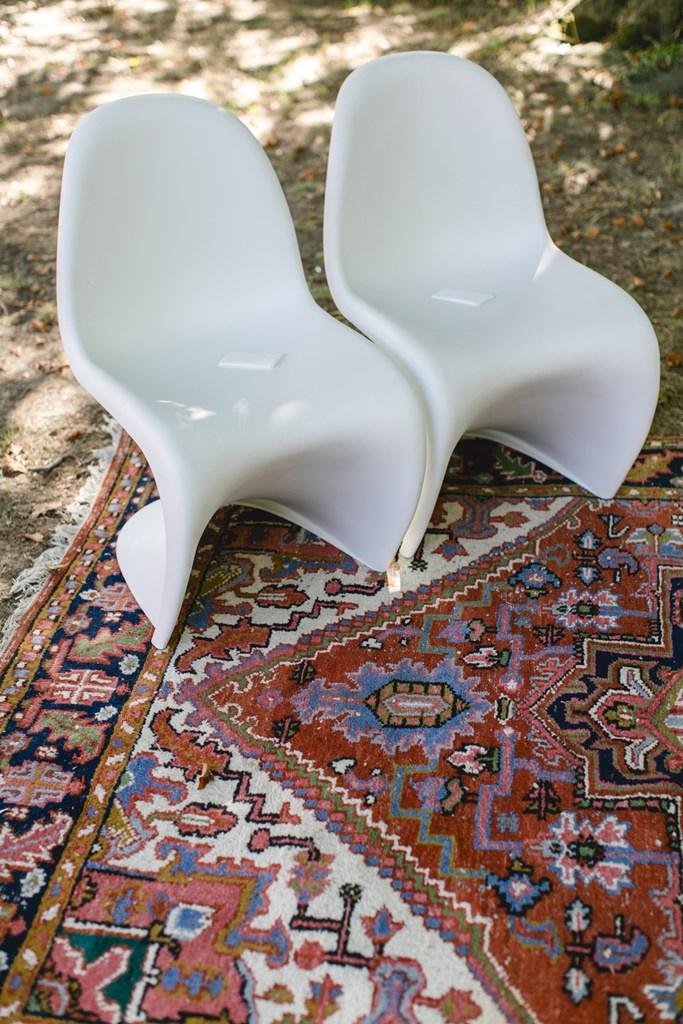 weiße Panton Chairs auf einem Teppich bei einer Freien Trauung im Boho-Stil