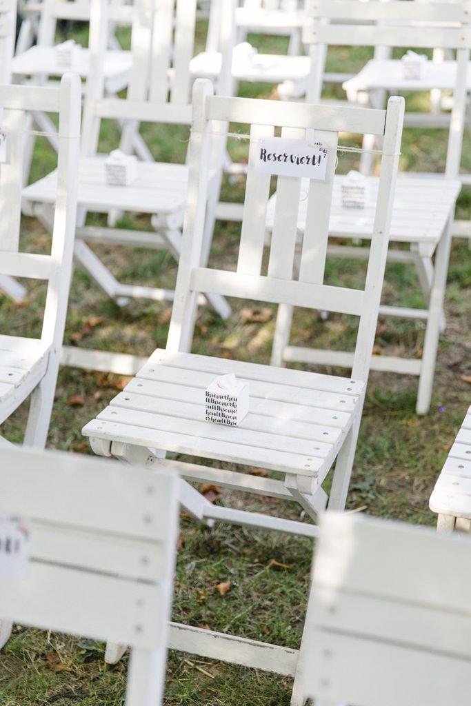 Freie Trauung Outdoor Deko:mit weißen Holzklappstühle auf denen Taschentücher Boxen stehen