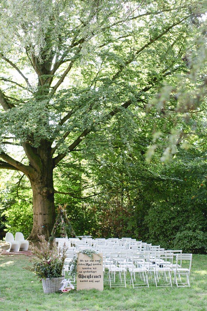 Blumendeko, Holzschild und weiße Stühle bei einer Freien Trauung draußen im Garten