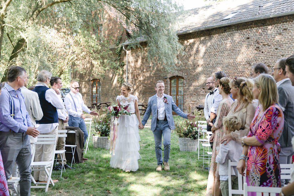 das Brautpaar schreitet durch die Gäste auf dem Weg zur Freien Trauung