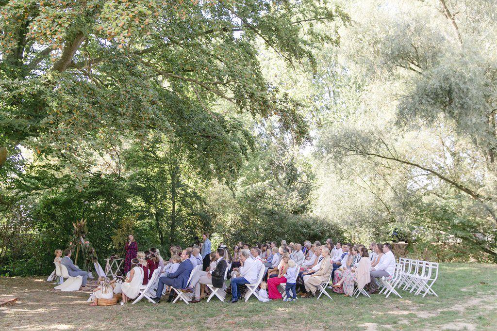Brautpaar und Gäste sitzen während der Freien Trauung auf Gut Hohenholz unter einer alten Eiche