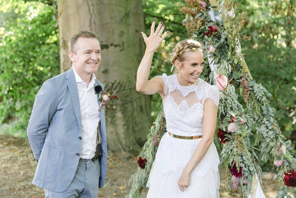 die Braut hält nach der Freien Trauung ihre Hand samt Ehering in die Luft