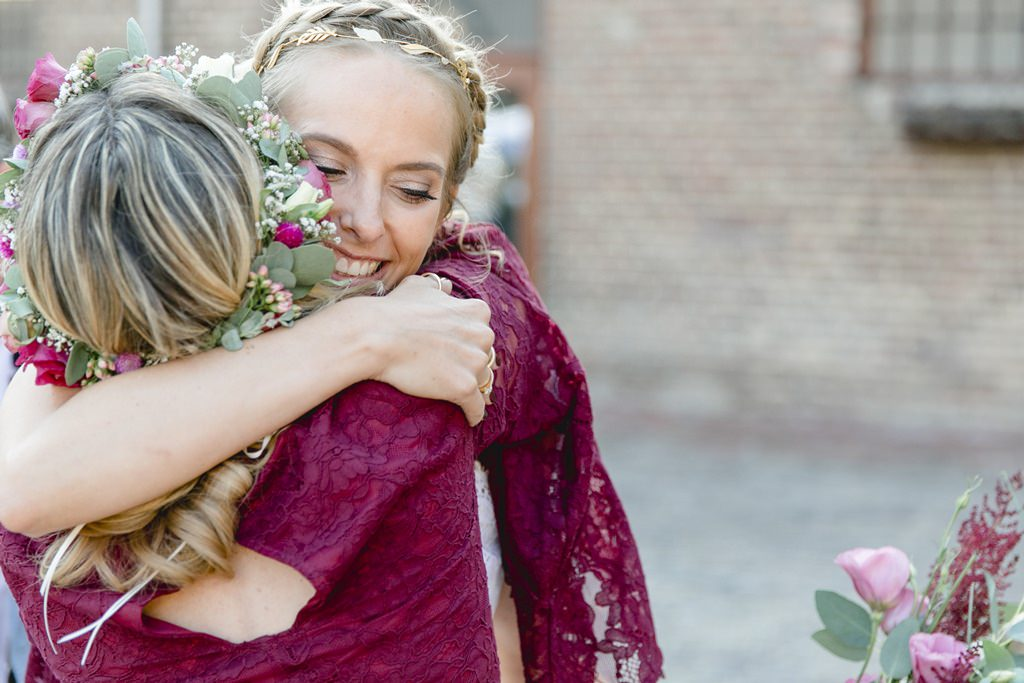 die Braut umarmt eine Brautjungfer nach der Freien Trauung