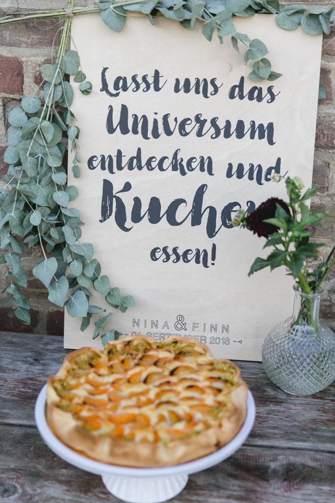 Kuchenbuffet mit lustigem Spruchschild bei einer Hochzeit