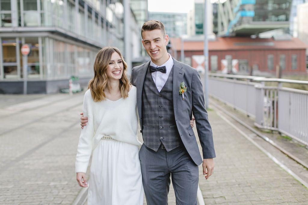 Braut und Bräutigam laufen Arm in Arm vor urbaner Kulisse