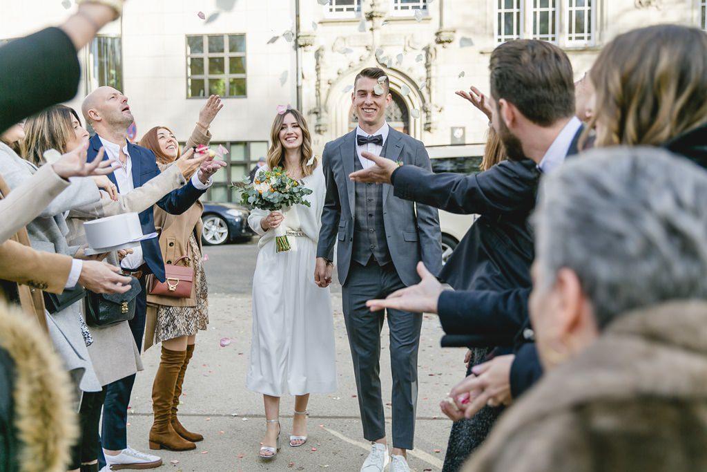 das Brautpaar wird beim Auszug aus dem Standesamt mit Rosenblättern beworfen