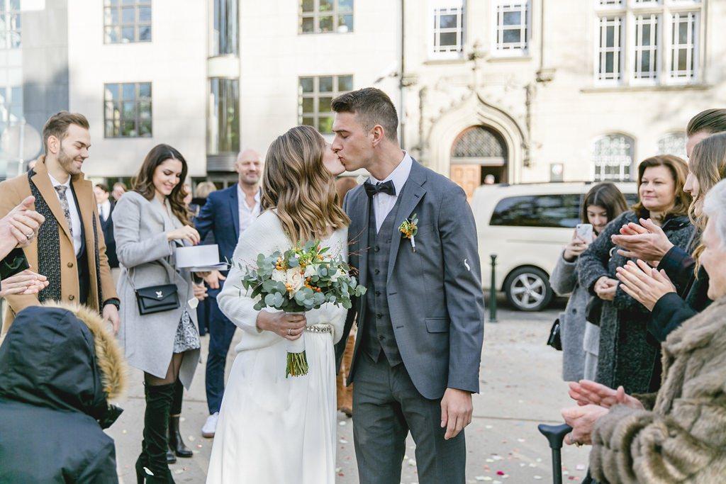 das Brautpaar küsst sich nach dem Auszug aus dem Standesamt