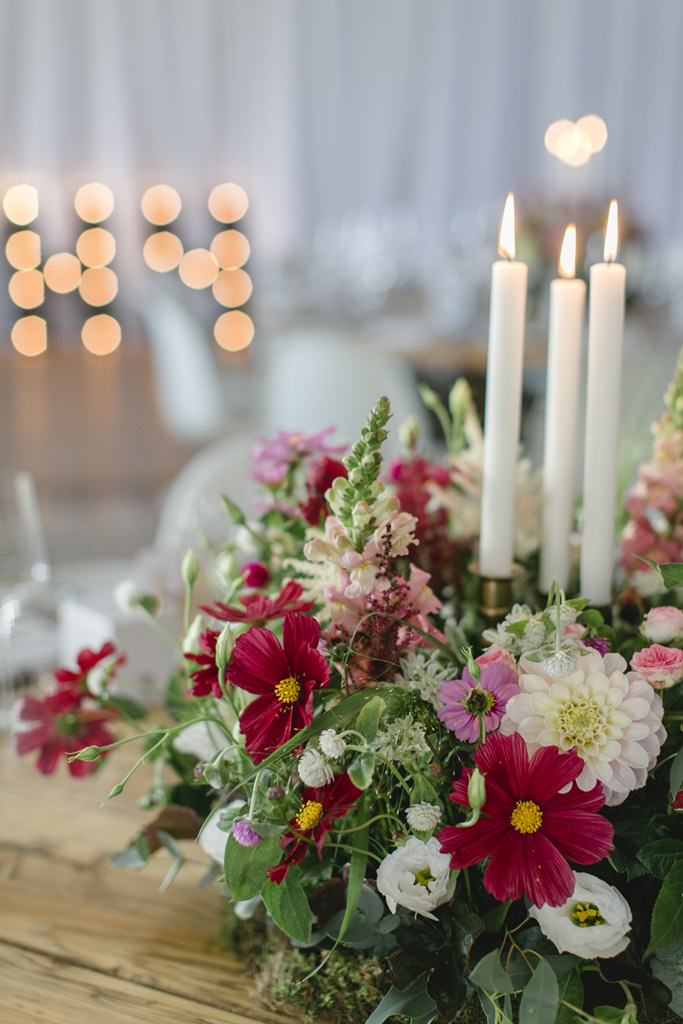 Hochzeitsdeko mit weißen Kerzen und Blumen in Bordeaux und Weiß