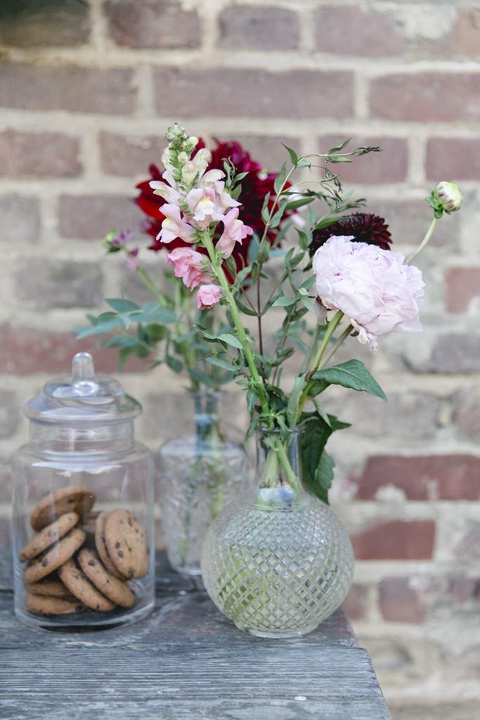 Glasvasen mit Blumen in Bordeaux, Zart- und Altrosé schmücken den Sweet Table einer Hochzeit