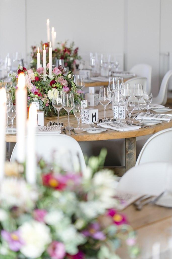 modern rustikale Hochzeitsdeko mit vielen Blumen und runden Holztischen