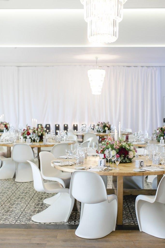 Hochzeitsfeier auf Gut Hohenholz mit weißen Panton Chairs und rustikalen Holztischen