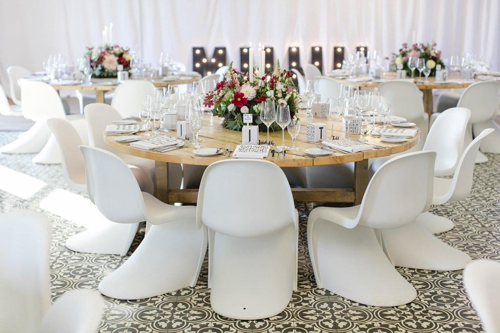 Hochzeitsdeko mit weißen Panton Chairs und rustikalen Holztischen