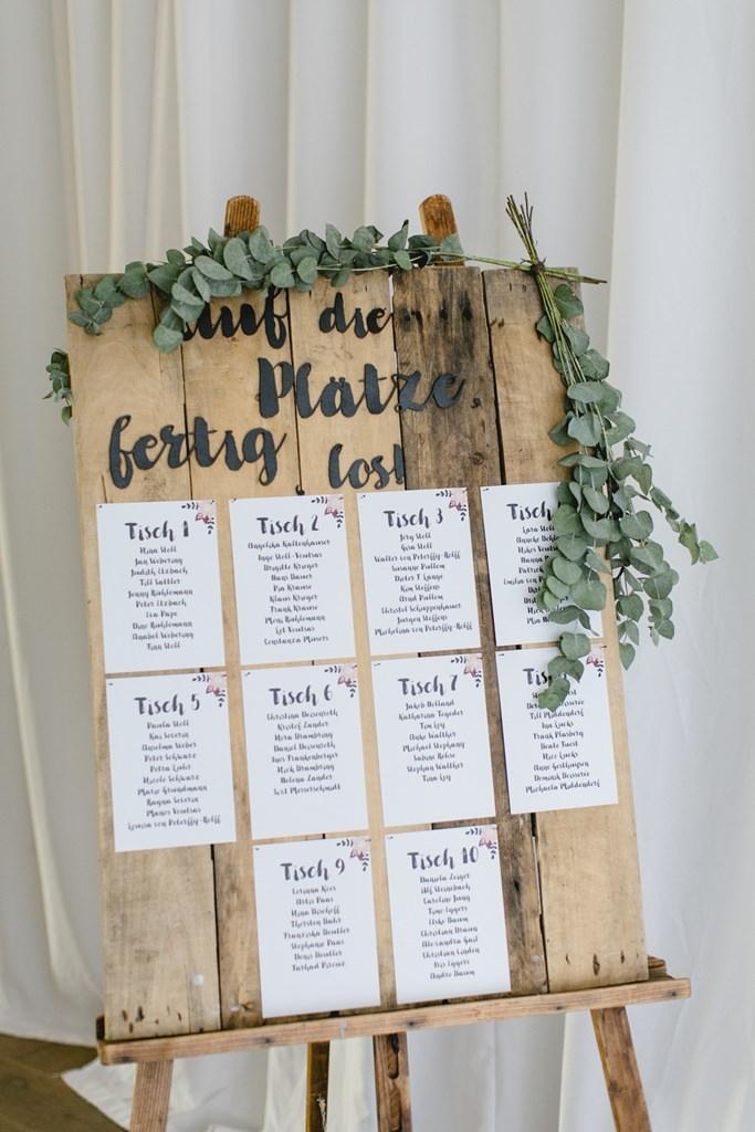 rustikale Holztafel mit Greenery Deko als Tischplan bei einer Hochzeit