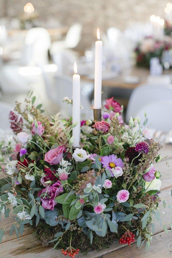 Kerzenleuchter, geschmückt mit Wiesenblumen als Hochzeitsdeko auf rustikalen Holztischen