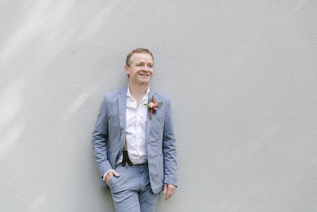 Hochzeitsfoto vom Bräutigam, der entspannt an einer Wand lehnt