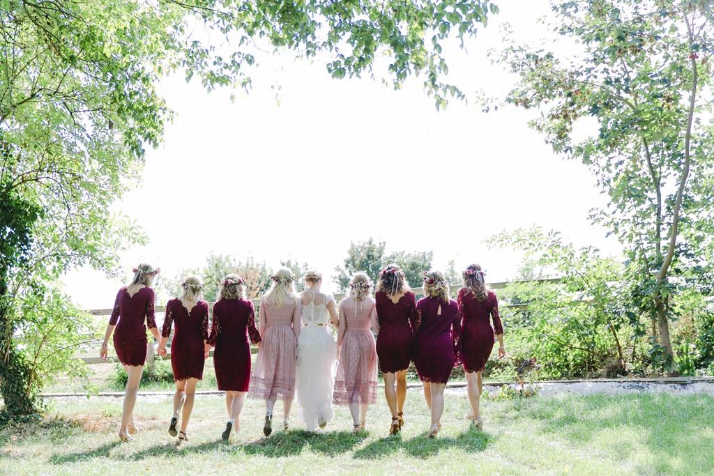 die Braut läuft mit ihren Brautjungfern über eine Wiese