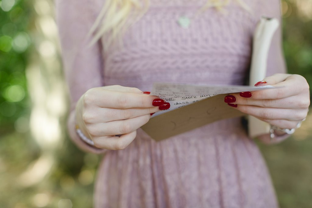 die Brautjungfer hält einen Brief der Braut in der Hand