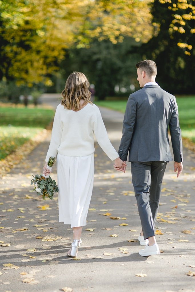 Paarshooting draußen: Das Paar läuft durch einen herbstlichen Park