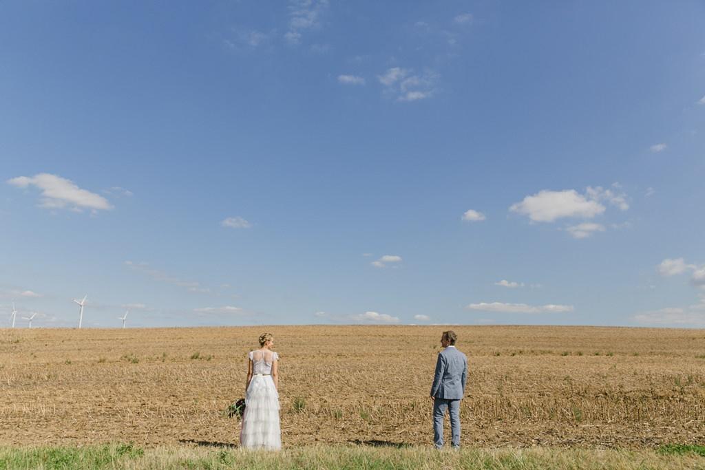 Braut und Bräutigam stehen auf einem großen Feld mit blauem Himmel im Hintergrund| fotografiert von Hanna Witte