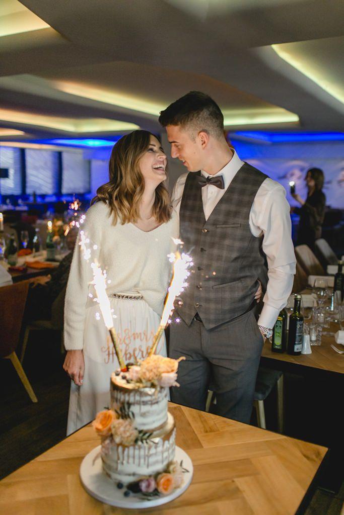 das Brautpaar steht hinter der Hochzeitstorte mit Tortenfeuerwerk