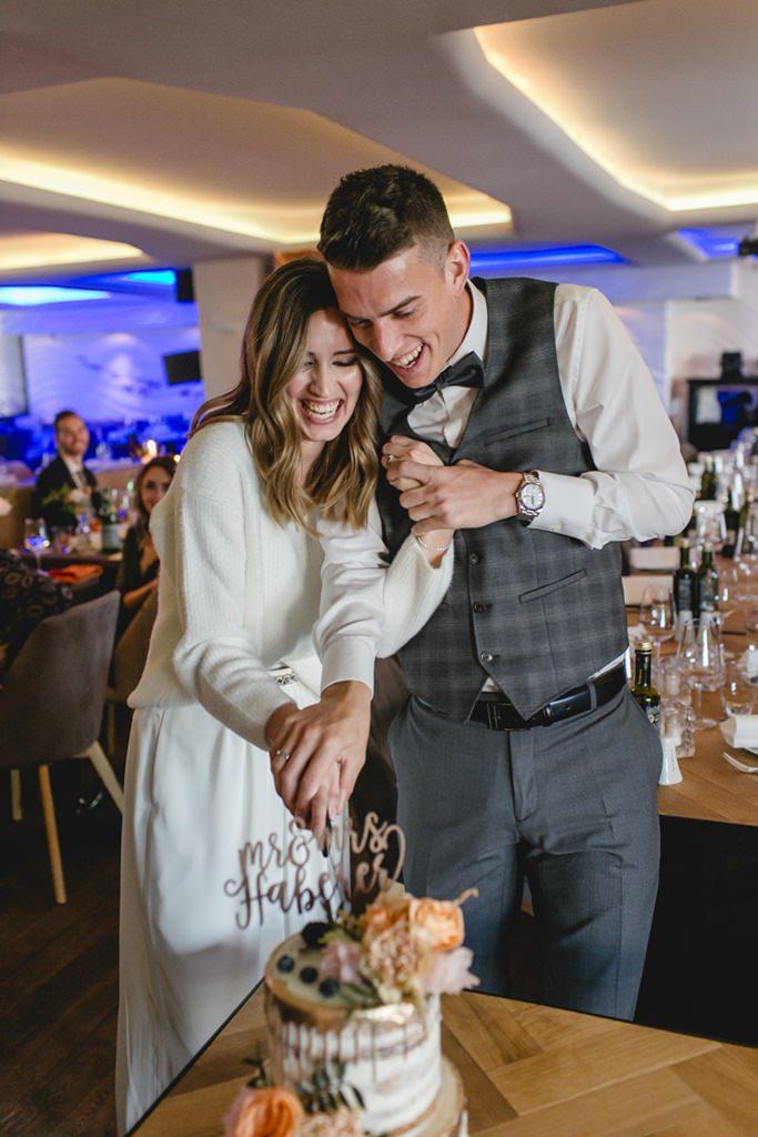 das Brautpaar beim Hochzeitstortenanschnitt